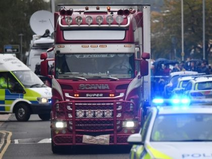 Police officers drive away a lorry (C) in which 39 dead bodies were discovered sparking a murder investigation at Waterglade Industrial Park in Grays, east of London, on October 23, 2019. - British police said 39 bodies were found near London Wednesday in the container of a truck thought to …
