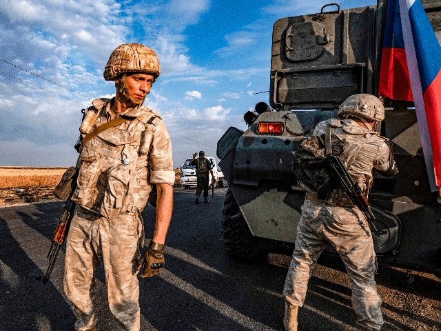 Russian military police members stand outside an armoured vehicle along a road in the countryside near the northeastern Syrian town of Amuda in Hasakeh province on October 24, 2019, as part of a joint patrol between Russian forces and Syrian Kurdish Asayish internal security forces near the border with Turkey. …