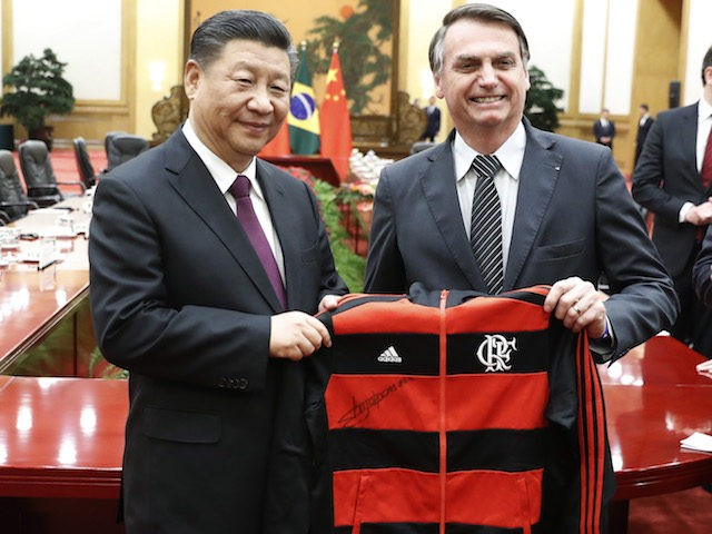 Brazil's President Jair Bolsonaro (R) gifts China's President Xi Jinping (L) a jacket at the end of the signing ceremony at the Great Hall of the People in Beijing on October 25, 2019. (Photo by Yukie Nishizawa / POOL / AFP) (Photo by YUKIE NISHIZAWA/POOL/AFP via Getty Images)