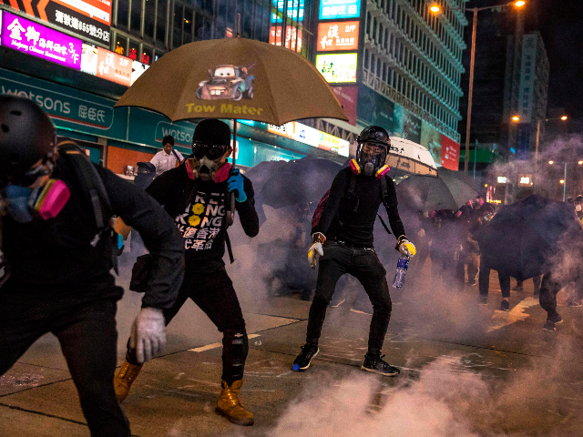 Pro-democracy protesters react after police fired tear gas in the Mong Kok district in Hong Kong on October 27, 2019. - Police fired tear gas and rubber bullets October 27 at pro-democracy protesters who defied authorities to hold a rally on Hong Kong's scenic harbourfront, the latest flashpoint in months …