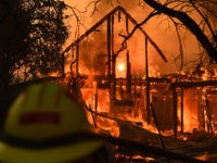 "The frame of a house still stands as it burns in front of the rising sun during the Kincade fire in Healdsburg, California on October 27, 2019. - Powerful winds were fanning wildfires in northern California in ""potentially historic fire"" conditions, authorities said October 27, as tens of thousands of …"