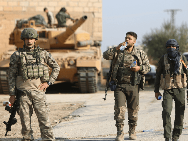 Turkish soldiers and a Turkey-backed Syrian fighter walk during a raid in a village east of Ras al-Ain on the border between Syria and Turkey in northeastern Syria, on October 28, 2019. (Photo by Nazeer Al-khatib / AFP) (Photo by NAZEER AL-KHATIB/AFP via Getty Images)