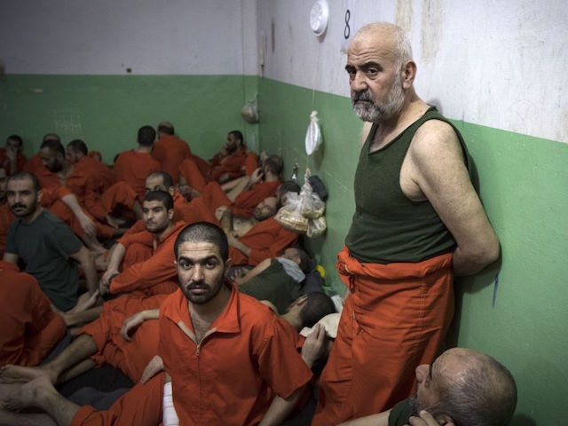 Men, suspected of being affiliated with the Islamic State (IS) group, gather in a prison cell in the northeastern Syrian city of Hasakeh on October 26, 2019. - Kurdish sources say around 12,000 IS fighters including Syrians, Iraqis as well as foreigners from 54 countries are being held in Kurdish-run prisons in northern Syria. (Photo by FADEL SENNA / AFP) (Photo by FADEL SENNA/AFP via Getty Images)