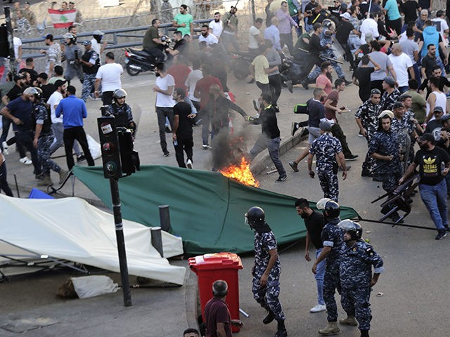 Lebanese security forces intervene to seperate between demonstrators counter-protesters in the capital Beirut's downtown district as the latter set fire to a tent during the 13th day of anti-government protests on October 29, 2019. - An unprecedented cross-sectarian movement has brought major cities across Lebanon to a standstill since October …