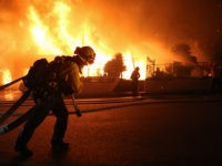 PORTER RANCH, CALIFORNIA - OCTOBER 11: Firefighters work at a house fire in the early morning hours during the Saddleridge Fire on October 11, 2019 in Porter Ranch, California. The fast-moving wind-driven fire has burned more than 4,000 acres and at least 23,000 homes are under mandatory evacuation orders. (Photo …