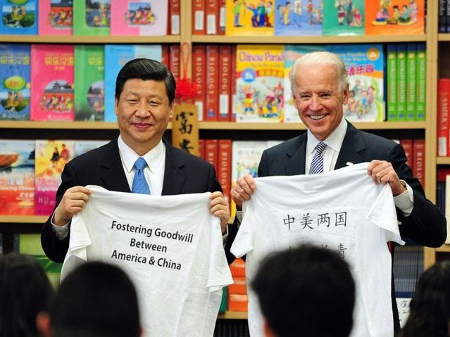 US Vice President Joe Biden and his Chinese counterpart Xi Jinping display shirts with a message given to them by students at the International Studies Learning School in Southgate, outside of Los Angeles, on February 17, 2012. Xi's trip is the first to Los Angeles by a top-level Chinese leader for 13 years, and California sees it as an opportunity to strengthen Chinese investment in the western US state's major shipping, tourism and entertainment industries. AFP PHOTO / Frederic J. BROWN (Photo credit should read FREDERIC J. BROWN/AFP/Getty Images)