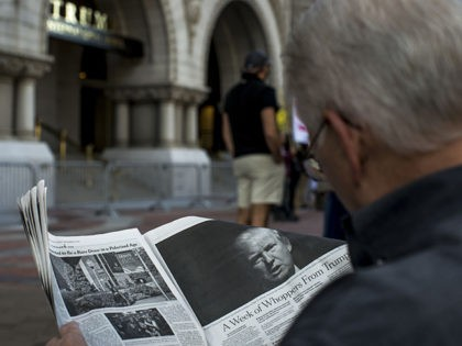 WASHINGTON, DC - OCTOBER 26: A man reads an article by The New York Times on Donald Trump during a protest outside the new Trump International Hotel at the old post office on October 26, 2016 in Washington, D.C. Republican presidential nominee Donald Trump will attend the hotel's grand opening. …