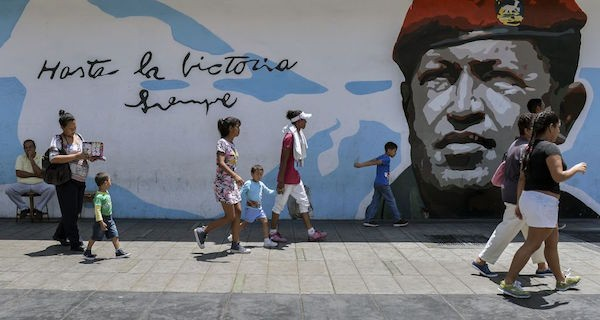 TOPSHOT - People walks by a graffiti with an image of late President Hugo Chavez in Caracas on May 11, 2018. - Venezuelan citizens will face presidential elections on May 20 amid a severe socio-economic crisis, with hyperinflation - estimated at 13,800% by the IMF for 2018 - and shortages of food, medicines and other basic products. (Photo by Luis ROBAYO / AFP) (Photo credit should read LUIS ROBAYO/AFP/Getty Images)