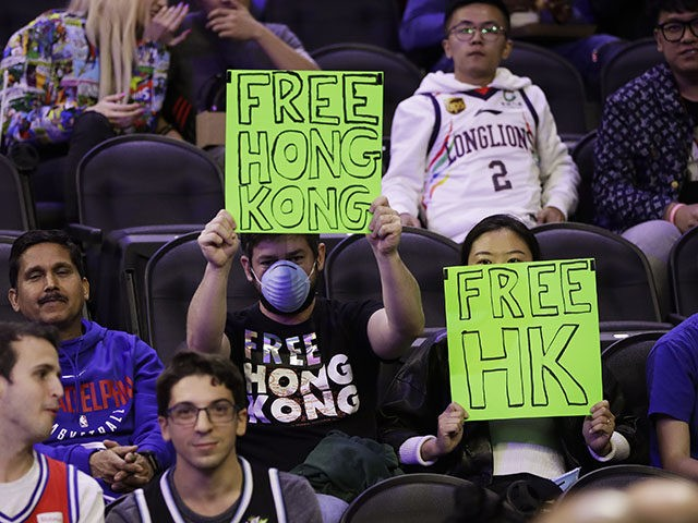 Fans hold signs ahead of a an NBA exhibition basketball game between the Philadelphia 76ers and the Guangzhou Loong-Lions on Tuesday, Oct. 8, 2019, in Philadelphia. (AP Photo/Matt Rourke)