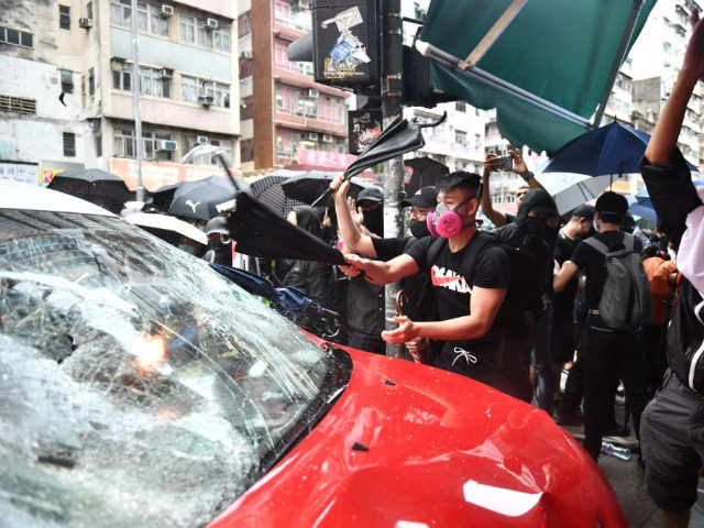 TOPSHOT - Protesters smash a taxi after the driver drove onto the pavement hitting two protesters along Cheung Sha Wan Road during a demonstration in Hong Kong on October 6, 2019. - A Hong Kong judge on October 6 rejected a challenge to an emergency law criminalising protesters wearing face …
