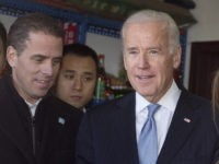 U.S. Vice President Joe Biden, center, buys an ice-cream at a shop as he tours a Hutong alley with his granddaughter Finnegan Biden, right, and son Hunter Biden, left, in Beijing, China Thursday, Dec. 5, 2013. (AP Photo/Andy Wong, Pool)