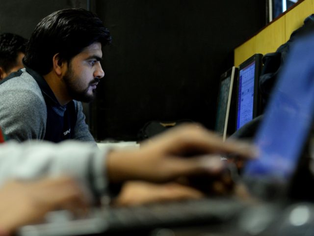 In this photograph taken on December 13, 2016, an employee of Indian IT security solutions company Innefu Labs works at their offices in New Delhi. In the darkened offices of a tech start-up, a handful of computer engineers sift through a mountain of intelligence data that would normally be the …