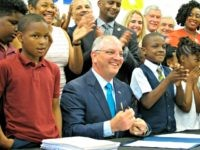 In this June 18, 2019, file photo, Gov. John Bel Edwards signs the Louisiana state operating budget for the upcoming year during a visit to Capitol Elementary School in Baton Rouge, La. A Republican group has responded to the start of Louisiana Gov. John Bel Edwards' TV campaign for re-election …