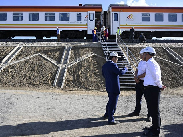 Contractors from China Commmunication Construction Company (CCCC) stand next to the Standard Gauge Railway (SGR) train at Mai Mahiu, on October 16, 2019. (Photo by SIMON MAINA / AFP) (Photo by SIMON MAINA/AFP via Getty Images)