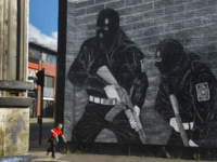 BELFAST, NORTHERN IRELAND - OCTOBER 13: A young boy runs past a loyalist paramilitary mural on the day that the new Loyalist Community Council was launched at the Park Avenue Hotel on October 13, 2015 in Belfast, Northern Ireland. The council has the backing of the three main loyalist paramilitary …