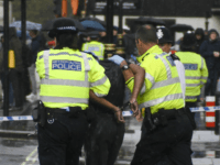 Police and medics respond to an incident outside the gates of the Houses of Parliament, in London, Tuesday, Oct. 1, 2019. Police in London have detained a man near the Houses of Parliament after he doused himself in what appeared to be flammable liquid. (AP Photo/Alberto Pezzali)