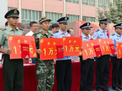 "This picture taken on August 3, 2014 shows uniformed personnel during an awarding ceremony for those who helped in the killing and capture of 10 ""suspected terrorists"" in Moyu county in Hotan prefecture, northwest China's Xinjiang region. China is offering more than 300 million yuan ($49 million) for residents of …"