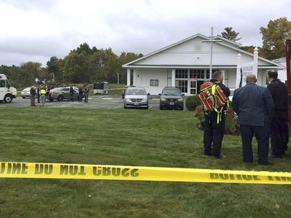 In this photo provided by WMUR-TV, police stand outside the New England Pentecostal Church after reports of a shooting on Saturday, Oct. 12, 2019, in Pelham, N.H. WMUR-TV reports that Hillsborough County Attorney Michael Conlon said a suspect is in custody. (Siobhan Lopez/WMUR-TV via AP)