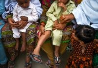 In this image taken on May 8, 2019, Pakistani women hold their HIV infected children as they gather at a house at Wasayo village in Rato Dero in the district of Larkana of the southern Sindh province. - Parents nervously watch over their children as they jostle in line to …
