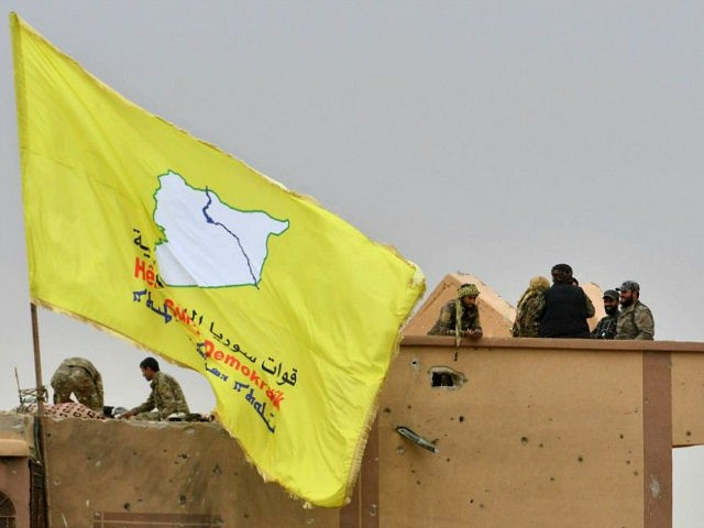 "Fighters of the Syrian Democratic Forces (SDF) stand atop a roof next to their unfurled flag at a position in the village of Baghouz in Syria's eastern Deir Ezzor province near the Iraqi border on March 24, 2019, a day after the Islamic State (IS) group's ""caliphate"" was declared defeated …"