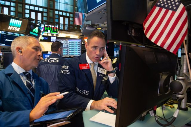 """Traders work on the floor at the opening bell of the Dow Industrial Average at the New York Stock Exchange on August 22, 2018 in New York. - Wall Street was poised Wednesday to observe the longest-ever """"bull market,"""" a run that began amid extraordinary crisis-era monetary policy and which …"""