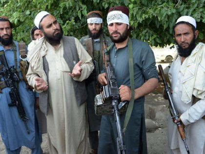 Afghan Taliban militants stand with residents as they took to the street to celebrate ceasefire on the second day of Eid in the outskirts of Jalalabad on June 16,2018. - Taliban fighters and Afghan security forces hugged and took selfies with each other in restive eastern Afghanistan on June 16, …