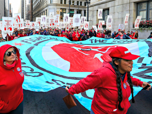 Teachers, staff and their supporters march through downtown Chicago, Monday, Oct. 14, 2019. The teachers are calling for district leaders to meet their demands on class sizes just days before a threatened strike that would affect thousands of students in the country's third-largest school district. (AP Photo/Teresa Crawford)