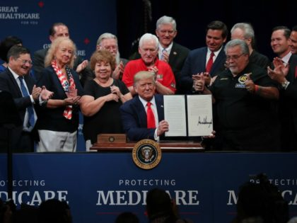 THE VILLAGES, FLORIDA - OCTOBER 03: President Donald Trump sits at a table to sign an executive order concerning Medicare during an event at the Sharon L. Morse Performing Arts Center on October 03, 2019 in The Villages, Florida. President Trump spoke about Medicare, and signed an executive order calling …