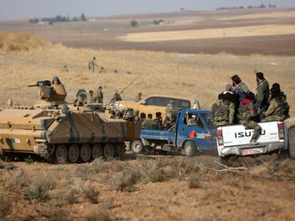 Turkey-backed Syrian fighters and Turkish troops gather at a position east of the northeastern Syrian town of Ras al-Ain, facing positions held by fighters from the Syrian Democratic Army (SDF), on October 28, 2019. (Photo by Nazeer Al-khatib / AFP) (Photo by NAZEER AL-KHATIB/AFP via Getty Images)