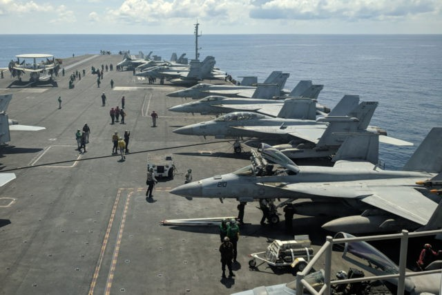 This photograph taken on October 16, 2019 shows US Navy F/A-18 Super Hornets multirole fighters and an EA-18G Growler electronic warfare aircraft (2nd R) on board USS Ronald Reagan (CVN-76) aircraft carrier as it sails in South China Sea on its way to Singapore. (Photo by Catherine LAI / AFP) …