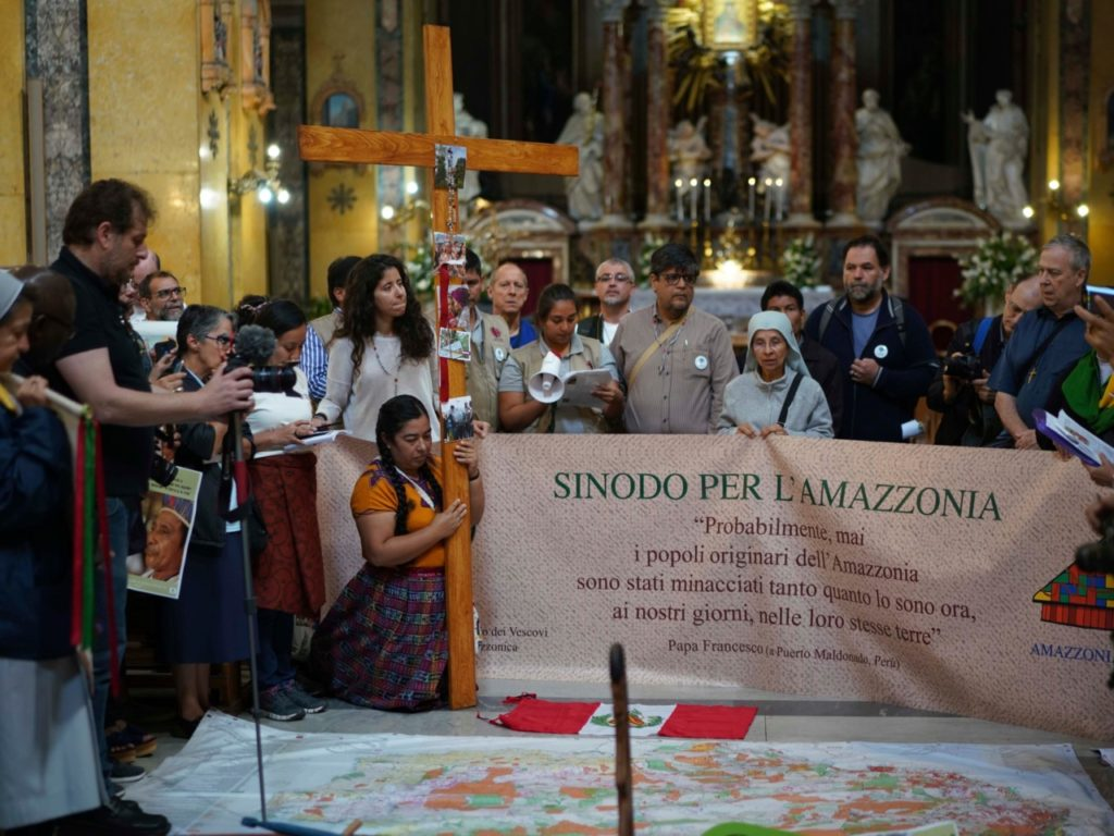 People pray and hold banner in Santa Maria in Transpontina Church, during a Via Crucis (Way of the Cross) procession of members of Amazon indigenous populations from St. Angelo Castle to the Vatican, Saturday Oct. 19, 2019. Pope Francis is holding a three-week meeting on preserving the rainforest and ministering to its native people as he fended off attacks from conservatives who are opposed to his ecological agenda. (AP Photo/Andrew Medichini)