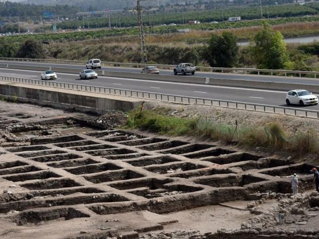 Cars drive Sunday on a highway past part of a vast 5,000-year-old cosmopolitan and planned city, one of the first and largest of the ancient Near East, excavated by the Israeli Antiquities Authority in En Esur, Israel. The archaeological site, located near Wadi Ara, was discovered before the construction of …