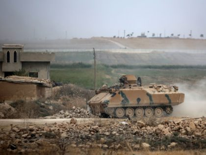 An armoured personnel carrier transports Turkey-backed Syrian fighters on the road between the Syrian towns of Tal Abyad and Kobani on the Turkish border on October 16, 2019 as Turkey and its allies continue their assault on Kurdish-held border towns in northeastern Syria. - Turkey rebuffed international pressure to curb …