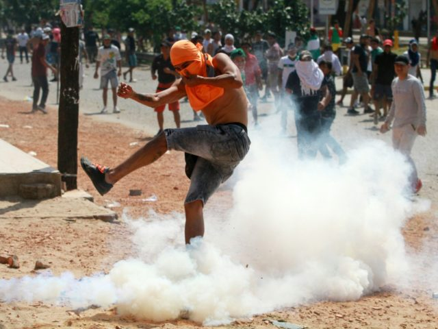 A supporter of Comunidad Ciudadana party returns a tear gas to police riot during clashes between supporters of Bolivian opposition candidate Carlos Mesa and of President Evo Morales over disputed poll results, in Santa Cruz, Bolivia, on October 23, 2019. - Bolivia's opposition launched a general strike on Wednesday amid …