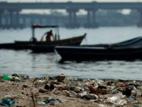 In this photo taken on Friday, June 15, 2012, a fisherman takes his boat onto a trash-ridden beach on Guanabara Bay near the international airport in Rio de Janeiro, Brazil. The throngs streaming into Rio for the United Nations Conference on Sustainable Development or Rio+20 may be dreaming of white-sand …