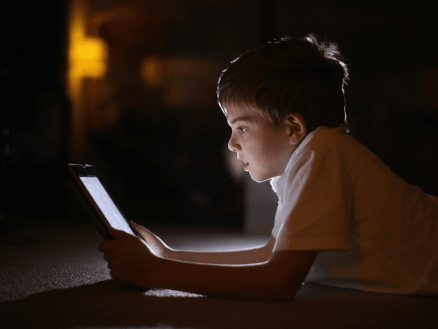 KNUTSFORD, UNITED KINGDOM - NOVEMBER 29: In this photograph illustration a ten-year-old boy uses an Apple Ipad tablet computer on November 29, 2011 in Knutsford, United Kingdom. Tablet computers have become the most wanted Christmas present for children between the ages of 6-11 years. Many parents are having to share …