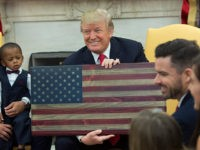 WASHINGTON, DC - DECEMBER 05: (AFP OUT) U.S. President Donald Trump holds a plaque made by Brian Steorts the owner of Flags of Valor during a meeting with Steorts and other business owners and their families to discussing tax reform in the Oval Office of the White House on December …