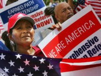 A woman joins hundreds of other immigrants during a rally in downtown Miami 01 May 2007. Tens of thousands of activists rallied across the United States to demand an overhaul of immigration laws and greater rights for the country's estimated 12 million illegal workers. AFP PHOTO/Roberto SCHMIDT (Photo credit should …