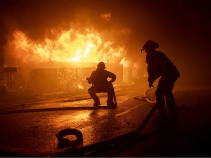 Firefighters try to save a home on Tigertail Road during the Getty fire, Monday, Oct. 28, 2019, in Los Angeles, Calif. (AP Photo/ Christian Monterrosa)