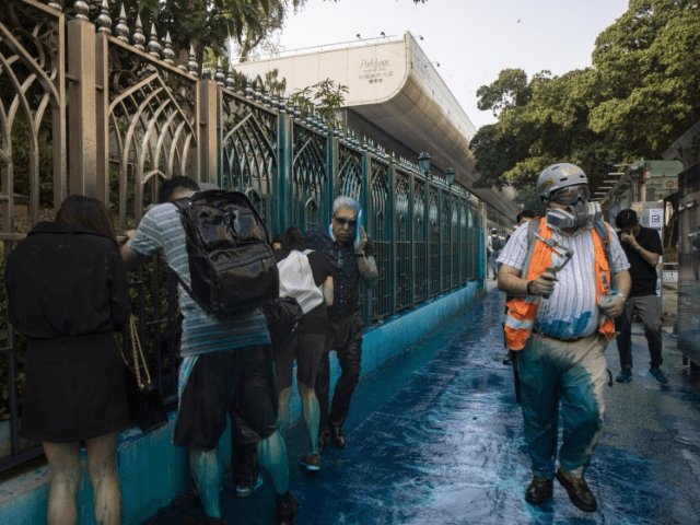 People react after sprayed with blue-dyed water by a police riot-control vehicle during a protest outside the Kowloon Mosque in Hong Kong. Hong Kong officials apologized to leaders of the Kowloon Mosque afterward.(Chan Cheuk Fai /Associated Press)
