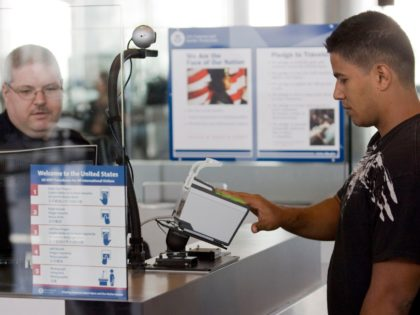 HOUSTON - FEBRUARY 1: U.S. Customs and Border Protection officer Thomas Wuenschel (L) monitors his screen as an arriving passenger uses a new biometric scanner at George H. W. Bush Intercontinental Airport February 1, 2008 in Houston, Texas. The new system is set up to scan all ten fingers instead …
