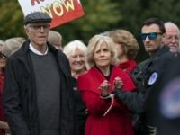 Actress and activist Jane Fonda, joined at left by actor Ted Danson, is arrested at the Capitol for blocking the street after she and other demonstrators called on Congress for action to address climate change, in Washington, Friday, Oct. 25, 2019. (AP Photo/J. Scott Applewhite)
