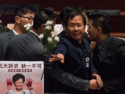 Pro-democracy lawmaker Kwok Ka-ki (C) is escorted by security after throwing flowers inside the chamber as Hong Kong Chief Executive Carrie Lam (not pictured) was holding a question and answer session at the Legislative Council (Legco) in Hong Kong on October 17, 2019. - Hong Kong's embattled leader Lam abandoned …