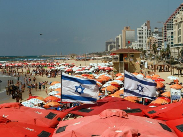 Israeli flags flutter above umbrellas on the beach in the Mediterranean city of Tel Aviv on August 11, 2015. Decision to dedicate a day of beach parties in the French capital to Israel's most famous beach city sparks condemnation from pro-Palestinian group saying it sends 'very bad message' of support …