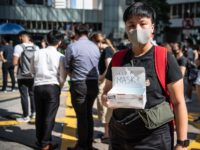 HONG KONG, CHINA - OCTOBER 4: A woman offers masks during a protest against a government ban on face masks in Central on October 4, 2019 in Hong Kong, China. Hong Kong's government invoked emergency powers on Friday to introduce an anti-mask law which bans people from wearing masks at …