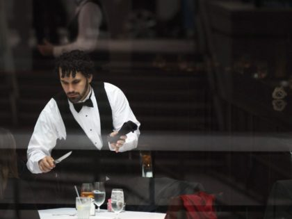 A waiter clears a table at a midtown restaurant popular for business lunches on November 22, 2011 in New York City. As retailers prepare for the start of the traditional holiday shopping season, the Commerce Department revised third-quarter GDP downward to 2 percent from 2.5 percent Tuesday for the quarter …
