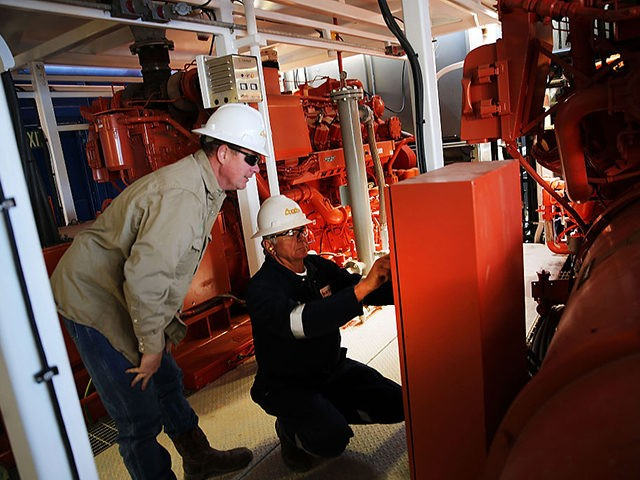 MENTONE, TX - FEBRUARY 05: Workers with Apache Corp. are viewed at the Patterson 298 natural gas fueled drilling rig on land in the Permian Basin on February 5, 2015 in Mentone, Texas. The rig, which is only 21 days old, is the first drilling rig in Texas that is …