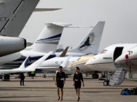 This photo taken on April 11, 2016 shows two crew members walking past business jets ahead of the 2016 Asian Business Aviation Conference and Exhibition (ABACE 2016) at Shanghai Hongqiao Airport in Shanghai. Some of China's wealthier investors are buying private jets to secure a mobile, dollar-denominated hedge against volatile …
