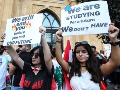 Lebanese demonstrators carry placards as they take part in a rally in the capital Beirut's downtown district on October 20, 2019. - Thousands continued to rally despite calls for calm from politicians and dozens of arrests. The demonstrators are demanding a sweeping overhaul of Lebanon's political system, citing grievances ranging …