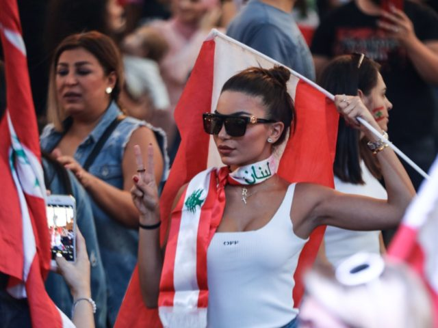 A Lebanese demonstrator waves a national flag at the Martyrs' Square in the centre of the capital Beirut on October 27, 2019, during ongoing anti-government protests. - Tens of thousands of Lebanese protesters successfully formed a human chain running north-south across the entire country today to symbolise newfound national unity. …